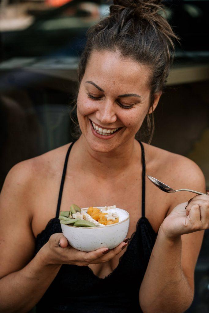 Femme qui sourit en mangeant