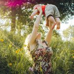 femme heureuse avec son enfant dans la végétation