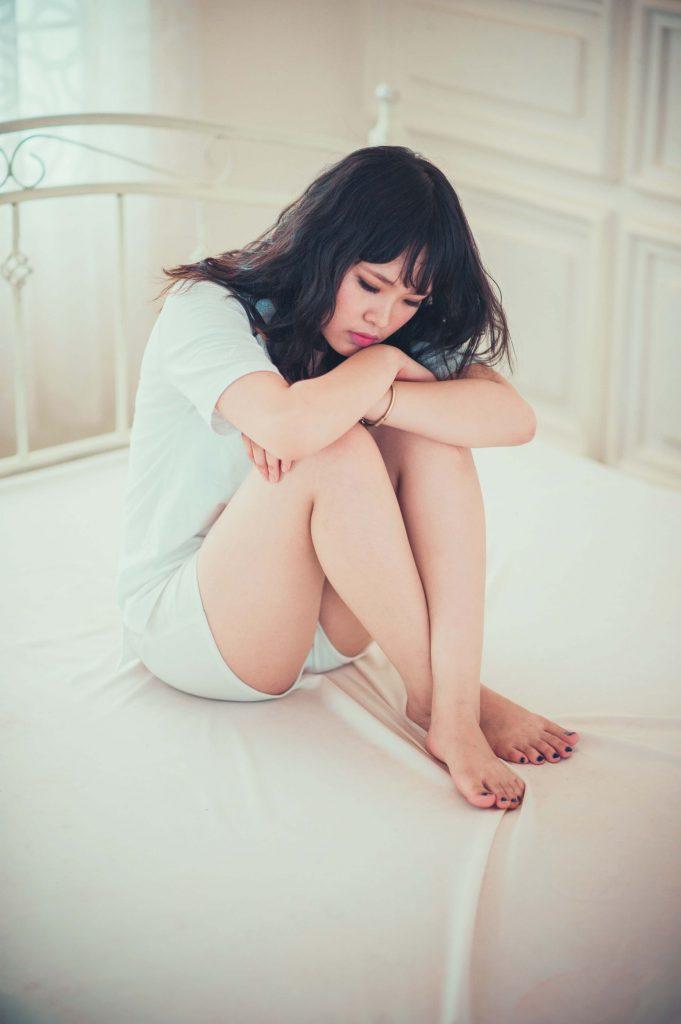 Jeune femme dans son lit qui a mal au ventre